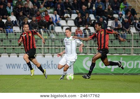 KAPOSVAR, HUNGARY - OCTOBER 15: Benjamin Balazs (in white 18) in action a Hungarian National Championship soccer game - Kaposvar (white) vs Honved (red) on October 15, 2011 in Kaposvar, Hungary.