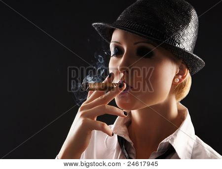 Young attractive female gangster smoking cigar over dark background