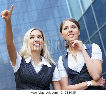 Two attractive business women over modern street background