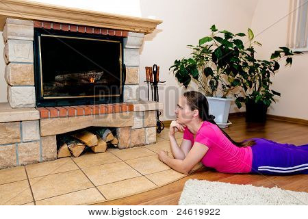 Beautiful girl warms by fireplace