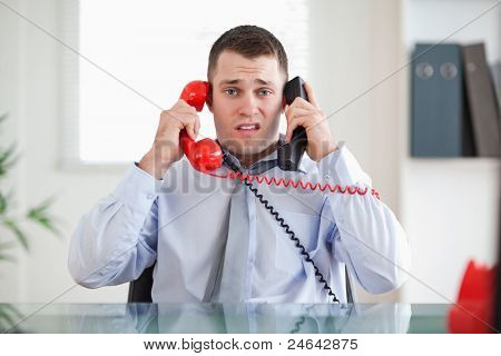 Stressed businessman unable to cope the telephone
