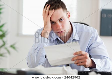 close up of young businessman worried about invoice