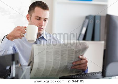 Young businessman having a coffee while reading the newspaper