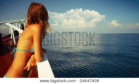 Young woman in swimsuit standing on a shipboard and looking to the sea