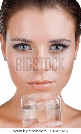 Close Up Of Beautiful Woman's Face, She Is Holding A Glass Of Clean Water