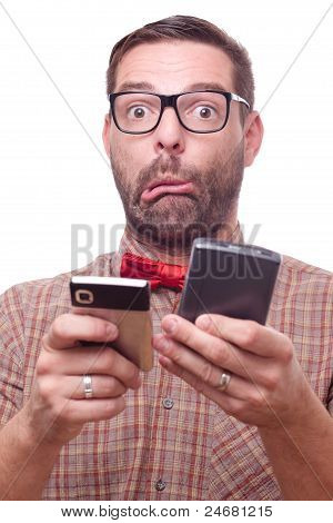 Confused Geeky Man With Two Gadgets, Making A Face. Isolated On White.