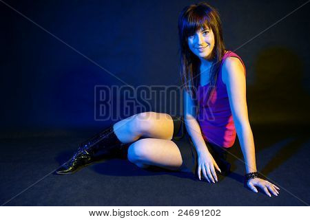 Girl in disco light sitting on black background.