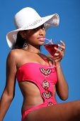 stock photo of monokini  - Beautiful young african american woman with happy smile wearing pink monokini swimsuit and sun hat sitting in sunshine drinking cocktail from martini glass - JPG