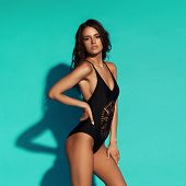 Young Sexy Slim Tanned Woman In Black Swimsuit Posing Against Blue Background. Full Length Fashion P poster