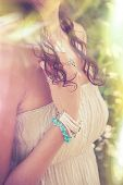 closeup of young woman hand with  lot of boho style jewrly, rings and bracelets outdoor summer day l poster
