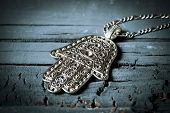 closeup of an old hamsa amulet, also known of the hand of fatima or the hand of mary, on a gray rust poster