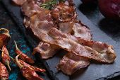 Slices of tasty smoked and fried bacon served as snack or breakfast poster