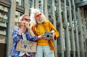 Street Performance. Two Inspired Hippies Wearing Bright Original Glasses Acting In Street Performanc poster