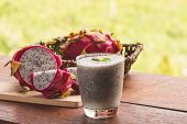 A Glass Of Dragon Fruit Smoothie And Fresh Dragon Fruit On Wooden Table poster