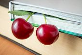 The Book And Red Ripe Cherries. Two Ripe Cherries Look Out Of The Book. Cherries As An Unusual Bookm poster