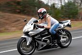 stock photo of crotch-rocket  - A woman drives a motorcycle at highway speeds with motion blur visible in the background - JPG