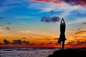 Sunset Meditation Silhouette. Active Woman Stand In Yoga Pose On Beach Rock To Keep Fit And Health.  poster
