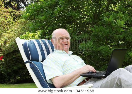 Pensioner Using Laptop In Garden