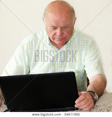 Elderly Pensioner Using A Laptop