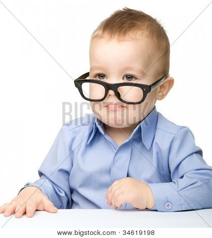 Portrait of a cute little boy wearing glasses and making funny grimace, isolated over white