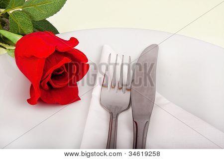 Closeup Of Rose, Plate And Silver Cutlery