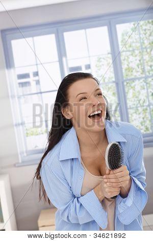 Happy woman acting as pop star, singing to hairbrush as microphone, laughing, having fun.