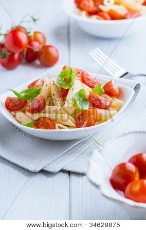 Bowl of pasta salad with cherry tomatoes on kitchen table