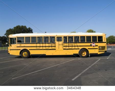 Yellow School Bus In School Parking Lot