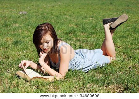 Young woman during warm sunny day, wearing dress, lying on grass relaxing and reading a book. Young girl with open holding book with one hand holding her chin and by another flipping pages.