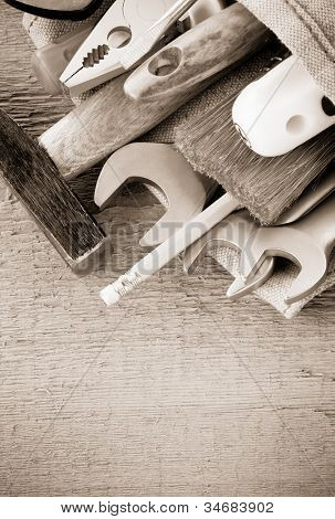 kit of tools and bag on wood background texture