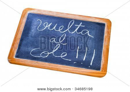 sentence back to school written in spanish (vuelta al cole) in a blackboard on a white background