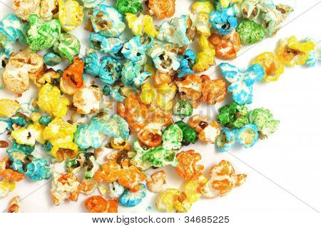 closeup of a pile of caramel corn of different colors on a white background