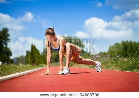 attractive female runner stretching before her workout