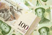 A Venezuelan One Hundred Bolivares Bank Note, Close Up In Macro On A Bed Of Chinese One Yuan Bank No poster