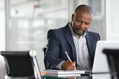 African serious businessman writing notes and using laptop. Mature business man writing his strategy poster