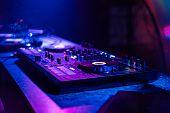 Professional Dj Mixer On Table In Nightclub poster