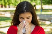 Unhealthy Brunette Girl Blowing Nose Into Tissue. Pretty Female Having Flu Or Allergy Against Blurre poster