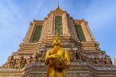 Golden Statue Of Standing Buddha Holding A Bowl With Ornated Temple On The Background. Wat Arun Or T poster