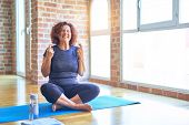 Middle age beautiful sportswoman wearing sportswear sitting on mat practicing yoga at home gesturing poster