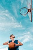 Sports And Basketball. A Young Teen In A Black Tracksuit Playing Basketball On The School Playground poster