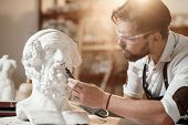 Professional Bearded Carver Polishing With Micro Drill Machine Details Of The Mans Sculpture Head In poster