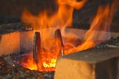 stock photo of blacksmith shop  - horseshoe in a forge in a flame - JPG