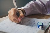 The Hand Of A Girl Student Holding A Pen To Test The Marks On The Notebook During The Examination. T poster