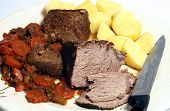 picture of pot roast  - A platter of pot roast steak some of it carved g with stewed carrot and onion and boiled potatoes - JPG