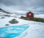 Typical norwegian red wooden house near famous Aurlandsvegen (Bjorgavegen) mountain road in Aurland, poster