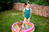Two Little Brother And Sister Playing And Splashing In Pool On Hot Summer Day. Children Swimming In  poster