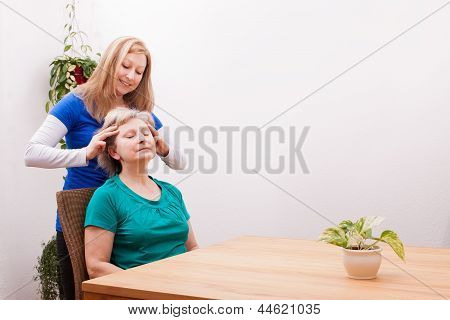 Blond Young Woman Massaging Female Seniors Scalp