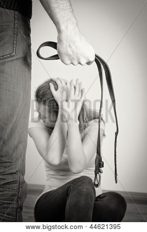 Man With Belt Coming To His Wife. Home Violence Concept. Black And White