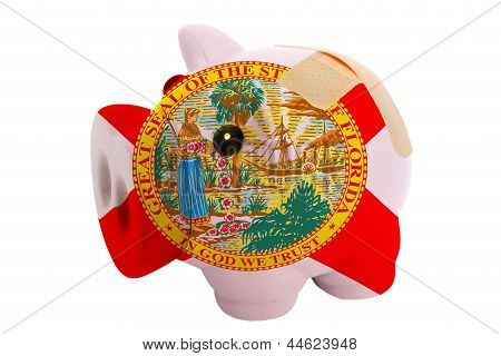 Closed Piggy Rich Bank With Bandage In Colors Flag Of American State Of Florida