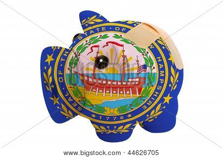 Closed Piggy Rich Bank With Bandage In Colors Flag Of American State Of New Hampshire